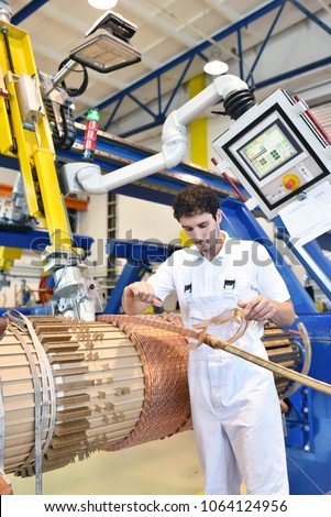 young mechanical engineering workers operate a machine for winding copper wire - manufacture of transformers in a factory  #1064124956