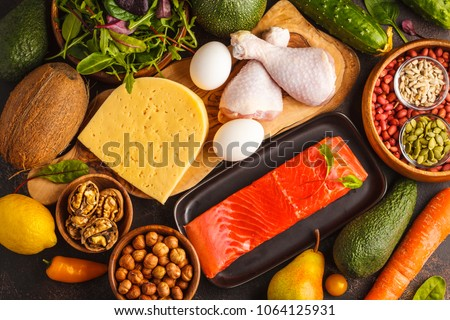 Keto diet concept. Ketogenic diet food. Balanced low-carb food background. Vegetables, fish, meat, cheese, nuts on a dark background. #1064125931