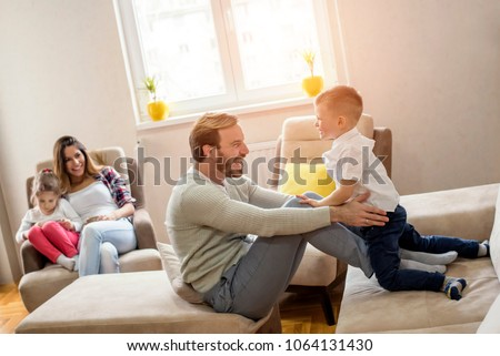 Parents with kid playing together and having fun in living room #1064131430