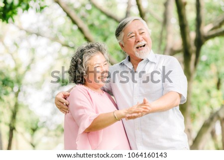 Happy senior Asian couple dancing in the park in sunny day #1064160143