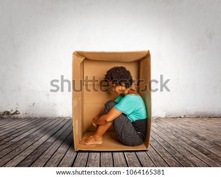 sad black woman inside a Box on a room