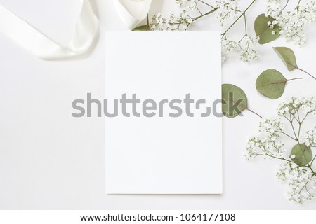 Styled stock photo. Feminine wedding desktop stationery mockup with blank greeting card, baby's breath Gypsophila flowers, dry green eucalyptus leaves, satin ribbon and white background. Empty space.  Royalty-Free Stock Photo #1064177108