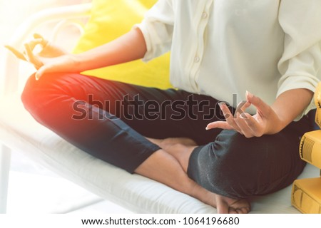 Attractive hold hand of beautiful woman meditates on long white chair with stack of colored books left beside her in living room.Businesswoman practicing yoga at home.Relax after work concept