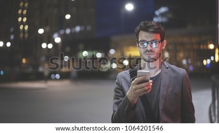 A young man is holding scrolling texting in his cellphone. A serious man calls for a taxi in an app in night time #1064201546