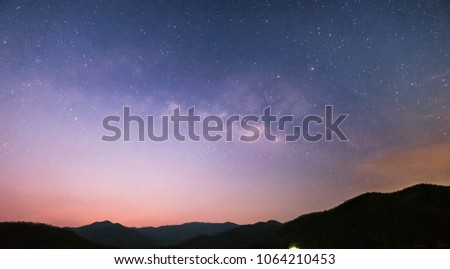 Mountain and river views at night The Milky Way and the Stars shine in the dark. #1064210453