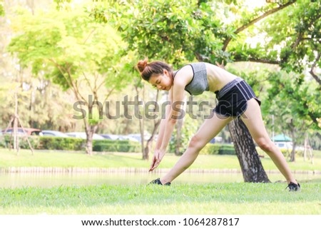 a Asian healthy slim body woman exercise or warm up in park in the morning #1064287817