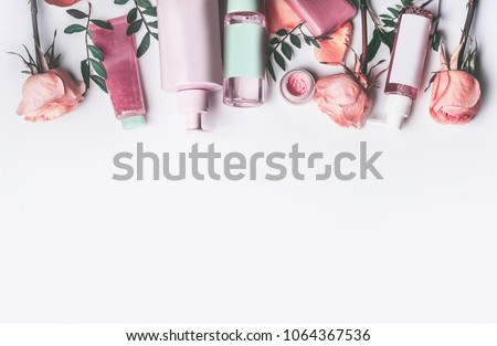 Cosmetics set with Rose essential oils: toner,serum, essence,moisturizer and and others on white desktop background, top view, border. Facial Skin care beauty treatment  #1064367536