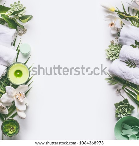 Green spa or wellness layout frame with towels, candle, tropical leaves , orchid flowers, succulents and body and face care tools and accessories on white background, top view.  Royalty-Free Stock Photo #1064368973