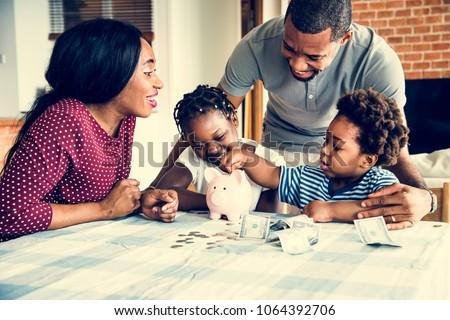 Family saving money to piggy bank Royalty-Free Stock Photo #1064392706