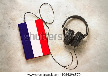 Headphones and book. The book has a cover in the form of a flag of France. Concept audiobooks. Learning languages. French language. #1064396570