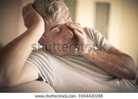Senior man tired sitting on bed.  Close up. #1064420288