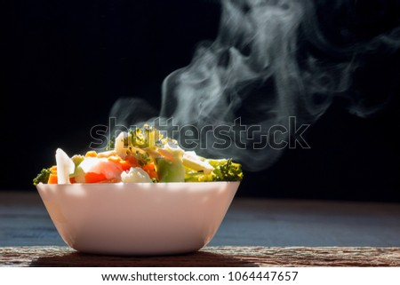 The steaming hot  from Mixed vegetables on white bowl dark background selective focus. #1064447657