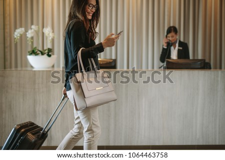 Woman using mobile phone and pulling her suitcase in a hotel lobby. Female business traveler walking in hotel hallway. #1064463758