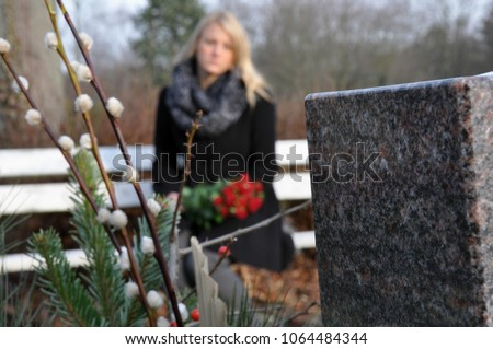 Woman in cemetery sits at a grave in deep sadness about death and loss Royalty-Free Stock Photo #1064484344