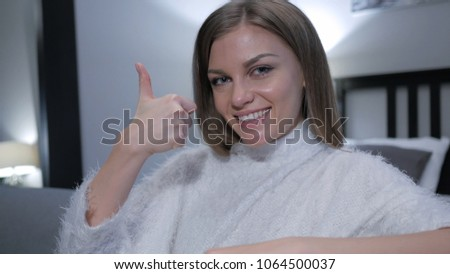 Thumbs Up by Casually Sitting Woman, Close up #1064500037