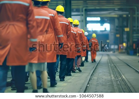 workers  helmets at the factory, view from the back, group of workers,  change of workers in the factory, people go in helmets and uniforms for an industrial enterprise #1064507588