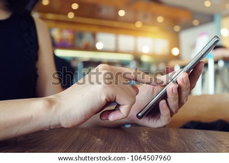 Woman with modern mobile phone in hands touching on a blank screen. Blurred cafe interior on a background. #1064507960