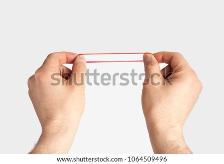 Red rubber band in hand. Elastic bands on hands.  dragging an elastic with hands.  #1064509496