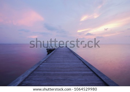 Wooden bridge on the sea in the port between beautiful Sunset. Horizon colorful sky twilight. Leave copy space in the sky Write a message. #1064529980