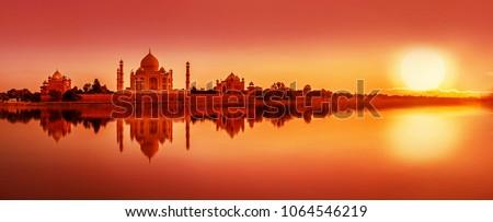 Panoramic view of Taj Mahal during sunset reflected in  Yamuna river, in Agra , Uttar Pradesh, India Royalty-Free Stock Photo #1064546219