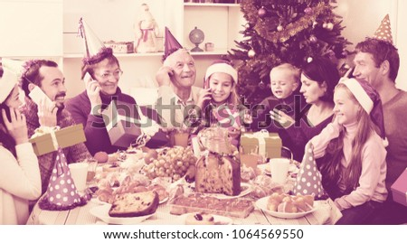 Large friendly smiling family enjoying their company during Christmas dinner #1064569550