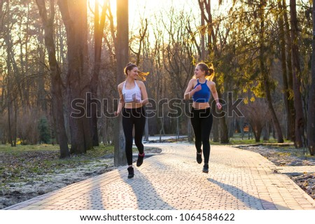 Two young women run along the path in the park at sunset and laugh  #1064584622