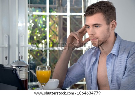 Handsome young man sitting at breakfast table with orange juice, cereal, coffee and fruit, smiling and using digital tablet  #1064634779