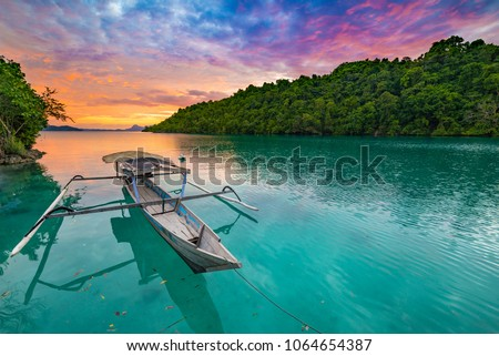 Togian Islands Indonesia sunset over caribbean sea, dramatic sky, traditional boat floating on blue green lagoon in the Togean Islands, Sulawesi, travel destination in Indonesia. #1064654387