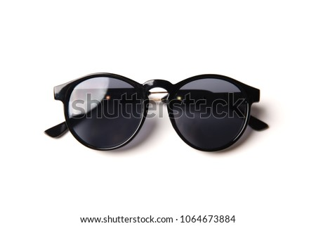 Stylish black sunglasses isolated on white background, top view Royalty-Free Stock Photo #1064673884