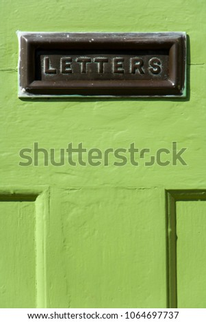 Old mail letter box in a distressed green house front door #1064697737