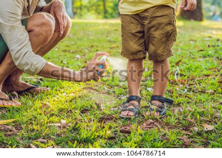 dad and son use mosquito spray.Spraying insect repellent on skin outdoor Royalty-Free Stock Photo #1064786714