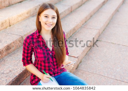 Cheerful young female student with cute smile taking notes. Girl with a mobile smart phone in her hands sitting on the steps in the park and writing on notebook. Education concept. #1064835842