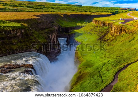 Grand Golden Waterfall on the Hvitau River. Sunny summer day. Huge masses of water crash into the abyss. The concept of extreme and phototourism #1064879423