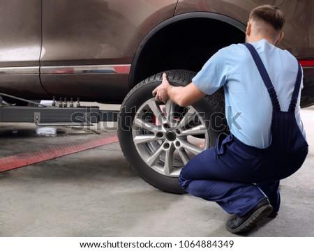Mechanic changing car wheel in garage. Tire service #1064884349