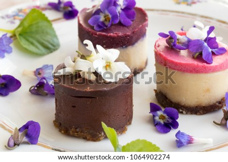 Raw vegan desserts on a plate with fresh violet and lungwort flowers #1064902274