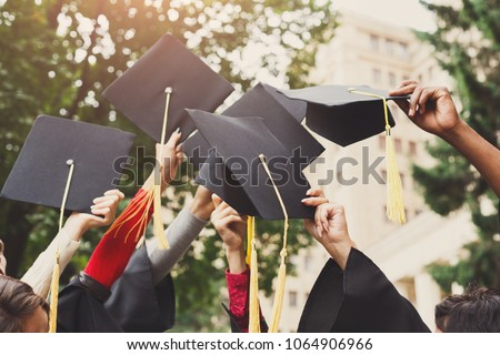 A group of multietnic students celebrating their graduation by throwing caps in the air closeup. Education, qualification and gown concept. #1064906966