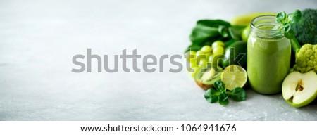 Glass jar mugs with green health smoothie, kale leaves, lime, apple, kiwi, grapes, banana, avocado, lettuce. Copy space. Raw, vegan, vegetarian, alkaline food concept. Banner. #1064941676
