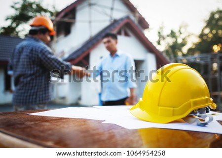 Shaking hands of partnership agreement between structural engineers and contractors to build houses. After agreeing the employment price and calculating the cost of construction and repair real estate Royalty-Free Stock Photo #1064954258