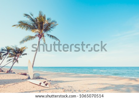Vintage surf board with palm tree on tropical beach in summer. vintage color tone
