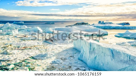 Global Warming and Climate Change - Icebergs from melting glacier in icefjord in Ilulissat, Greenland. Aerial picture of arctic nature iceberg and ice landscape. Unesco World Heritage Site.