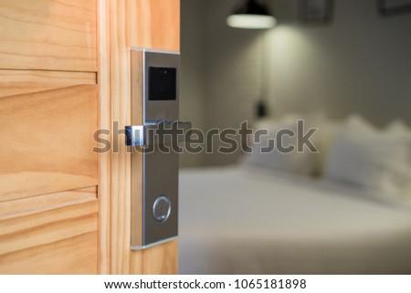 Hotel room , Condominium or apartment doorway with open door in front of blur bedroom background #1065181898