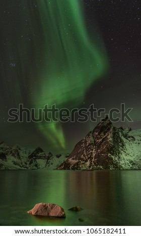 green northern lights (aurora borealis) over fjord with mountain in background #1065182411