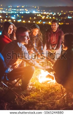 The happy people warming hands above the bonfire. evening night time #1065244880