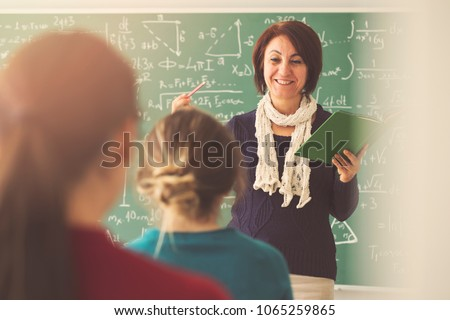 Teacher giving lesson to students in classroom Royalty-Free Stock Photo #1065259865