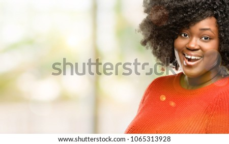 Beautiful african woman happy and surprised cheering expressing wow gesture, outdoor #1065313928
