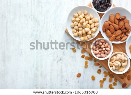 Different kinds of nuts in bowls and raisins on table, top view #1065316988