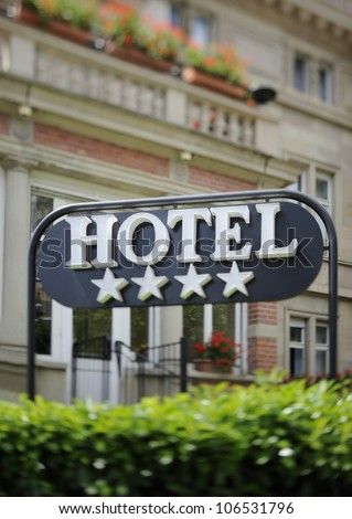 """Detail of a four stars hotel with beautiful building in the background. Tilt shift lens used to accent the word """"hotel"""" and to emphasize the background"""