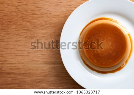French dessert and sweet snack concept with top view of a creme caramel, caramel custard or custard pudding in wooden rustic kitchen with copy space #1065323717