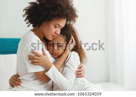 Mother comforting her daughter, sitting in the bedroom, hugging  Royalty-Free Stock Photo #1065324059