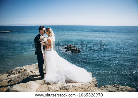 Beautiful wedding couple on their wedding photoshoot by the sea